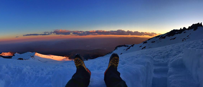 Mike Whitman enjoys the view while melting snow for the summit climb